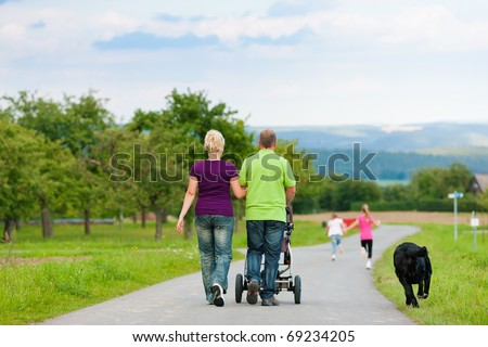 Family with three children (one baby lying in a baby buggy) walking down a path outdoors, two kids are running ahead, there is also a dog