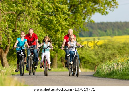 Family with three girls having a weekend excursion on their bikes on a summer day in beautiful landscape