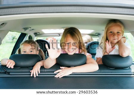 Family with three kids in a car