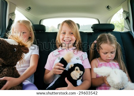 Family with three kids in a car, kids sitting on the backseats
