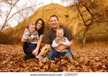 family with twin boys and pet dog at a park in Autumn