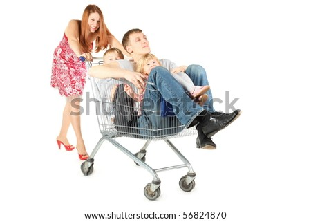 family with two children. father with son and daughter is sitting in shopping basket. woman is smiling. isolated.