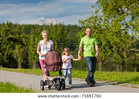 Family with two children (the baby lying in a baby buggy) walking down a path outdoors