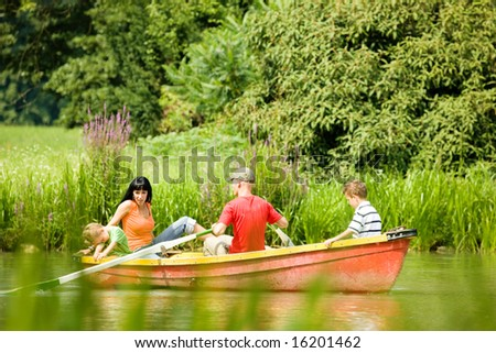 Family with two kids having a boat trip on a lake, in the background lots of trees and flowers