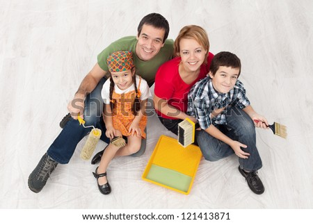 Family with two kids ready to pait their home - sitting on the protection foil, top view