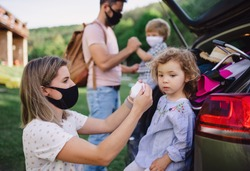 Family with two small children loading car for trip in countryside, wearing face masks.
