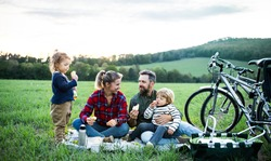 Family with two small children on cycling trip, sitting on grass and resting.