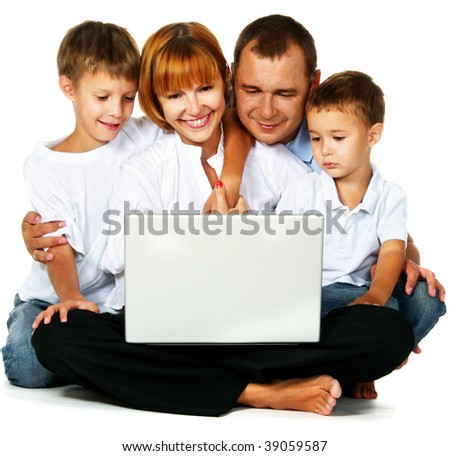 Family with two sons sitting on floor and using laptop computer