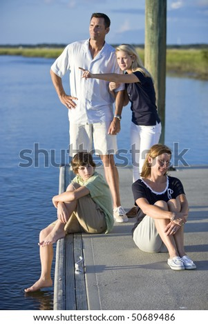 Family with two teenage children on dock by water, father and daughter watching and pointing