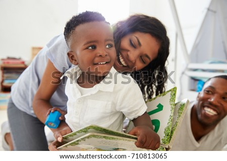 Family With Young Children Reading Book In Playroom Together