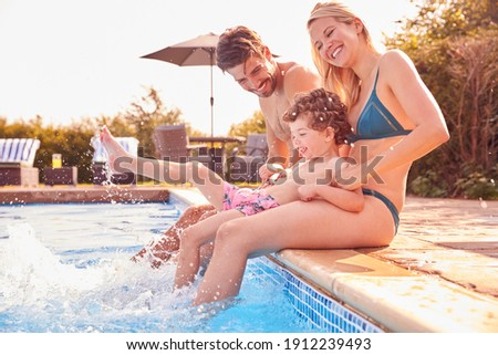 Family With Young Son Sitting On Edge Of Pool Having Fun On Summer Vacation In Outdoor Swimming Pool
