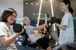 Family workout in the gym,smiling asian mother and daughter exercise with dumbbells,senior grandmother sit on the spinning bicycle,exercising togetherness,leisure activity,health care,fitness concept