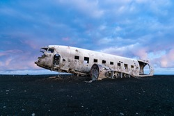 Famous abandoned plane wreck on Solheimasandur in Iceland. Old wreckage of airplane crashed in 1973 on black sand beach as tourist attraction. Douglas Dakota DC3, US navy. Traffic accidents concept.