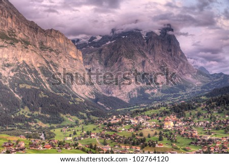 Famous alpine town Grindelwald in valley at sunset in front of mountain Eiger north face, Switzerland