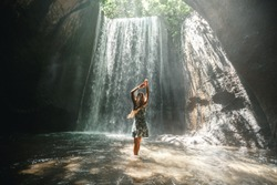 Famous Bali waterfall in the cave Tukad Cepung. Young girl tourist discover the beauty of earth