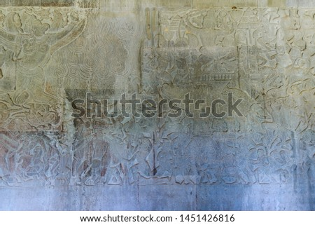 Famous bas reflief carved in the wall of Angkor Wat temple, world heritage and most visited tourist site, Cambodia. Details, close up of epic battles rock carving.