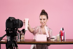 Famous blogger. Cheerful female vlogger is showing cosmetics products while recording video and giving advices for her beauty blog. Focus on digital camera