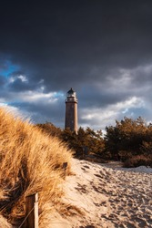 Famous brick lighthouse Darßer Ort Leuchturm with sand and dunes landscape and moody dark winter storm clouds. German Baltic Sea coastline at Fischland-Darss-Zingst in Mecklenburg
