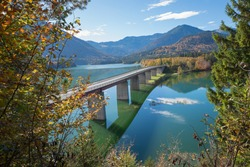 famous bridge over accumulation lake sylvenstein, upper bavaria. framed with autumnal trees. view from lookout point.