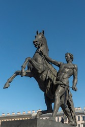 Famous bronze sculpture of young man taming horse at an Anichkov bridge on Nevsky Prospect in St. Petersburg against the blue sky