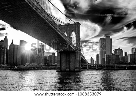 Famous Brooklyn Bridge in New York City, USA with financial district, downtown Manhattan in background. East River and beautiful sunset reflection. Black and white contrast photography, low angle view