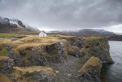 Famous building under the Snaefellsjokull volcano and glacier in Arnarstapi, Snaefellsnes peninsula, Iceland. Dramatic icelandic landscape, lonely house on the volcanic cliffs seacoast. Icelandic