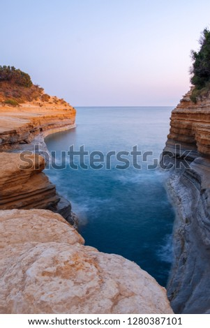 Famous Canal d'Amour beach with beautiful rocky coastline in amazing blue Ionian Sea at sunrise in Sidari holiday village on Corfu island in Greece