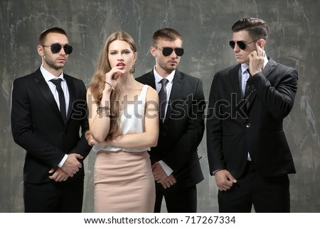 Famous celebrity with bodyguards on grunge background