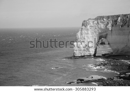 Famous chalk cliffs at Cote d'Albatre (Alabaster Coast). Etretat, France. Aged photo. Black and white. #305883293