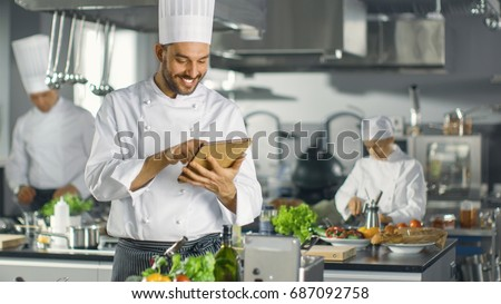 Famous Chef Uses Tablet Computer for Recipes While Working in a Modern Kitchen. His Help Work in the Background. #687092758