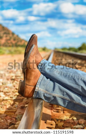 famous cow-boy boots and feets across train tracks