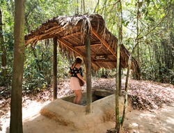 Famous Cu Chi tunnels. Tourist girl entering the tunnel.