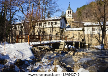Famous Dryanovo monastery in Bulgaria, entrance from the river and the bridge covered with snow in the winter. - stock photo