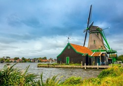 Famous Dutch Landscape -  village with a windmill and a house.   Agricultural Historical Landscape. Tourism. Popular Holland, Netherlands, Europe.