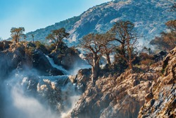 famous Epupa Falls on the Kunene River in Northern Namibia and Southern Angola border. Sunrise sunlight in water mist. This is africa. Beautiful landscape.