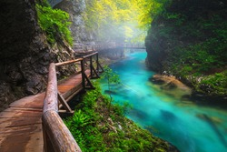Famous foggy Vintgar gorge with wooden footbridge over the Radova river after summer rain. Popular hiking and touristic place, Slovenia, Europe