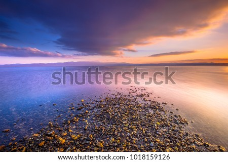 Famous Four elements of water earth, air and fire combined in sunrise at the mediterranean island of Lesbos, Greece #1018159126