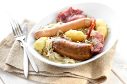 famous french speciality , alsacian sauerkraut on a white plate on a white wooden background