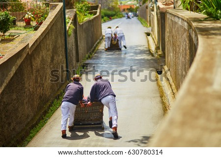 Famous fun tourist activity in Funchal, Madeira island, Portugal. Toboggan riders pushing wooden sledge with tourists downhill with high speed #630780314