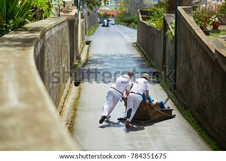 Famous fun tourist activity in Funchal, Madeira island, Portugal. Toboggan riders pushing wooden sledge with tourists downhill with high speed #784351675