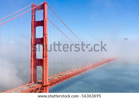 Famous Golden Gate Bridge in San Francisco partly covered in fog - stock photo