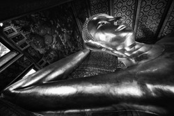 famous golden reclining buddha statue at wat pho bangkok thailand in black and white