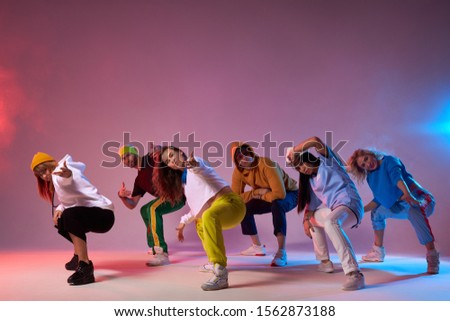 Famous group finish dancing , sitting on squats, looking at audience, making come alone gesture, expressing cheerfulness, dressed in sportswear, hip hop, street dance , break dance concept Stockfoto ©