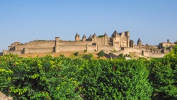 Famous hilltop town or ancient fortress La Cité de Carcassonne with medieval citadel or castle Château Comtal, surrounded by double walls, dotted by 52 towers and turrets, founded in Gallo-Roman times