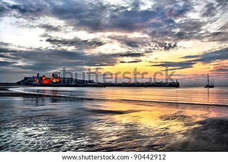 Famous historic Peel Castle with Dramatic sunset sky and reflection on the beach. HDR Effect. Isle of Man
