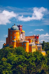 Famous historic Pena palace part of cultural site of Sintra against sunset sky in Portugal. Panoramic View Of Pena Palace, Sintra, Portugal. Pena National Palace at sunset, Sintra, Portugal.
