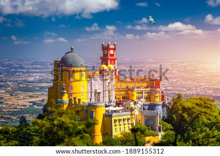 Famous historic Pena palace part of cultural site of Sintra against sunset sky in Portugal. Panoramic View Of Pena Palace, Sintra, Portugal. Pena National Palace at sunset, Sintra, Portugal.  Foto stock ©