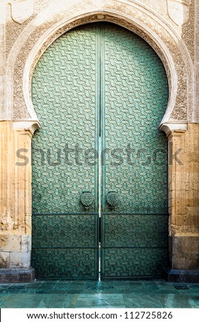 Famous landmark in Spain. Beautiful cathedral Mezquita of Cordoba, Andalucia. Green door with arch in old arabic style. Traditional spanish architecture. Religious and tourist place in Europe.