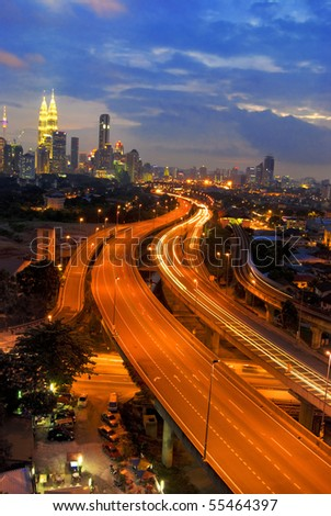 famous landmark of kuala lumpur with fast moving vehicle on highway
