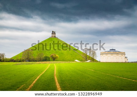 Famous Lion's Mound (Butte du Lion) memorial site, a conical artificial hill located in the municipality of Braine-l'Alleud comemmorating the battle of Waterloo, on a cloudy day in summer, Belgium